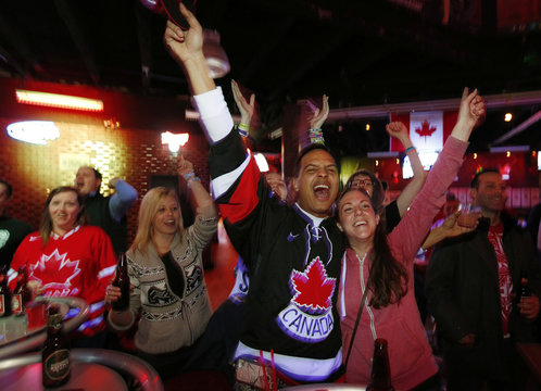 Team Canada hockey fans celebrate their team's win against Team USA at the men's ice hockey semi-final game at the Sochi 2014 Winter Olympic Games, at Cowboys Bar in Calgary.