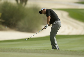 Howell of England hits a shot near the eighth green during the first round of the Dubai Desert Classic at the Emirates Golf Club