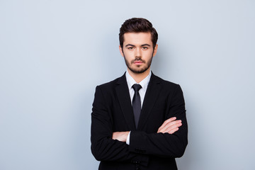 Portrait of handsome strict employer in formal clothes standing with crossed hands against gray background