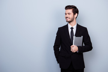 Handsome young successful happy businessman in black suit holding digital tablet against gray background