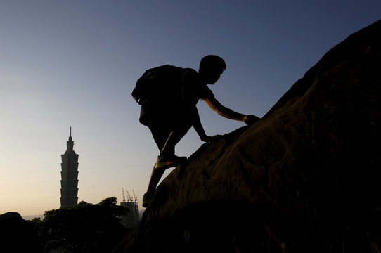 A man climbs a rock in front of Taiwan's landmark building Taipei 101 in Taipei, Taiwan