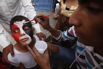 An anti-government protester paints the face of a boy with colours of Yemen's national flag in Sanaa