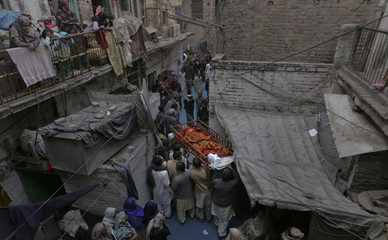 Family members lift the shroud-draped body of 62-year-old heart patient Chaudhry Mohammad Gulab in Lahore