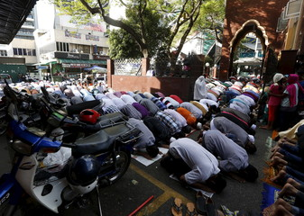 Foreign workers pray on the street outside a mosque during Eid Al-Fitr prayers in Kuala Lumpur