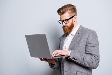 Close up of serious confident concentrated red bearded man in formal wear typing on his laptop on pure background, he is an economist