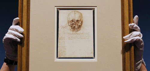 """An employee poses with artist Leonardo da Vinci's drawing """"A skull sectioned, 1489"""" at the Queen's Gallery at Buckingham Palace in London"""