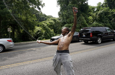Protester sprays his friends with a water bottle during a protest march in Ferguson