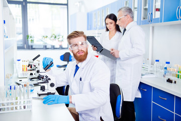 Portrait of young handsome bearded stylish intern, who is wearing gloves and labcoat, safety glasses. Behind him are people who are working for same experiment