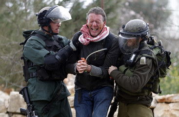Israeli border policemen detain a foreign activist during clashes following a demonstration against Jewish settlements in the West Bank village of Bilin