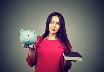 Cost of college education. Thoughtful woman balancing piggy bank and book