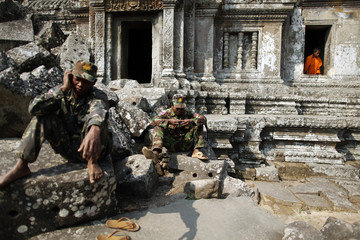 Buddhist monk looks through the window of 11th-century Preah Vihear temple as Cambodian soldiers pass time at border between Thailand and Cambodia