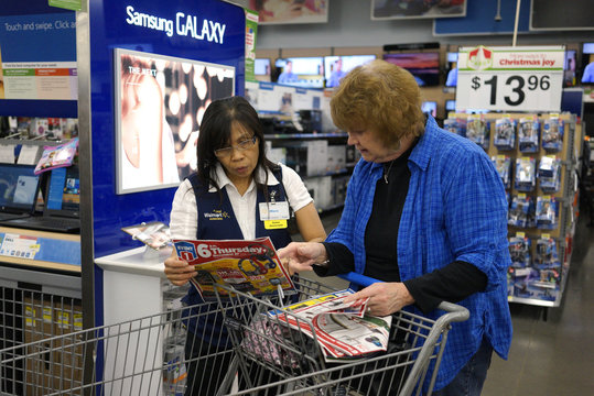 A Walmart employee helps a customer navigate a Black Friday sale flyer at the store in Broomfield