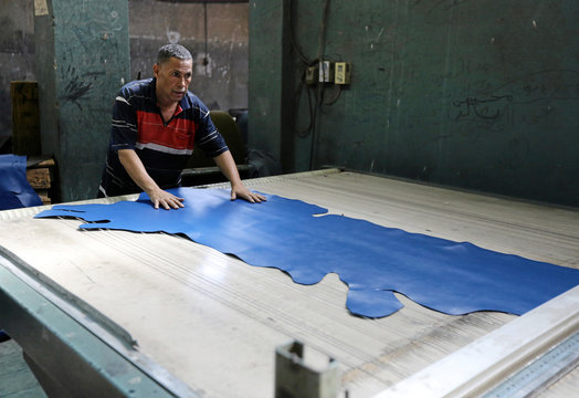 """A labourer works in a leather tannery workshop where Co-founders of a local brand """"Okhtein"""", sisters Aya and Mounaz Abdelraouf purchase leather in Cairo"""