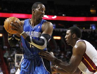 Orlando Magic's Dwight Howard looks to pass against the defense of Miami Heat's Dexter Pittman during first quarter pre-season NBA basketball game in Miami