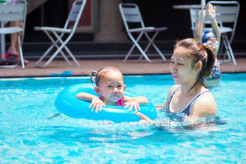 Mother teaches children to swim.