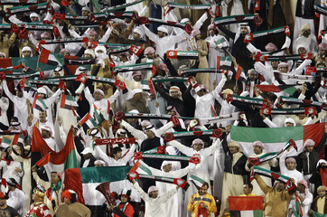 Fans of UAE hold up their national flag before their Asian Cup soccer match against Iraq in Doha