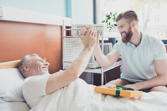 Give me five! Young stylish red bearded guy is visiting and cheering up his grandpa lying in bed at hospital ward
