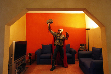Street artist Ruben Oviedo, dressed as comics superhero Thor, poses for a portrait in the living room of his home in Mexico City