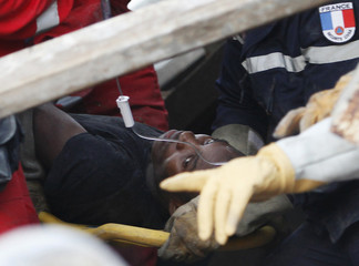 A man is taken to an ambulance after being rescued from the wreckage of the Hotel Napoli Inn and supermarket in downtown Rue du Centre, in Port-au-Prince