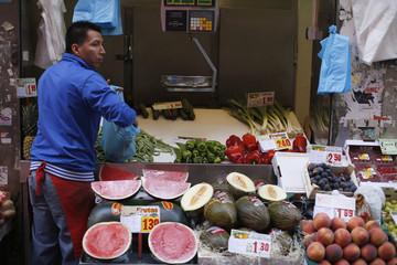Fruit vendor fills bag at a market in Madrid