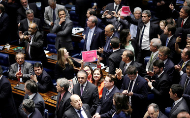 Senators react after the final session of voting on suspended Brazilian President Dilma Rousseff's impeachment trial in Brasilia