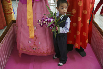 Sibb holds flowers between his parents standing in a pink coffin during their wedding ceremony at Wat Takien temple in Nonthaburi province