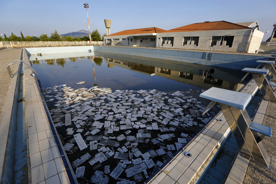 Garbage floats in a deserted swimming pool at the Olympic Village in Thrakomakedones