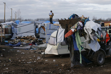 """A bulldozer clears away debris from makeshift shelters that are torn down in a section of the camp for migrants called the """"jungle"""", in Calais"""