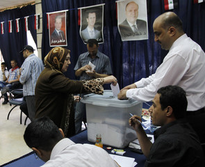 People cast their ballots during a presidential election at a polling centre in Damascus