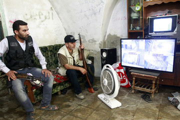 Members of the Free Syrian Army watch camera surveillance screens in the Bab al-Nasr neighborhood of Aleppo