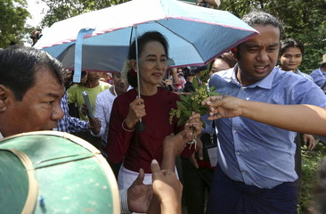 Myanmar pro-democracy leader Aung San Suu Kyi accepts flowers from supporters as she visits poling stations at her constituency Kawhmu township