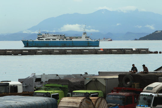 Truck drivers sit on top of a truck with a ferry in the background at Merak port near Cilegon, Banten province