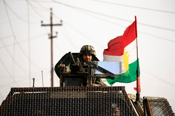 A member of Peshmerga forces rides in a military vehicle in the town of Bashiqa