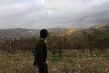 A Free Syrian Army fighter looks at a rainbow at the Jabal al-Akrad area in Syria's northwestern Latakia province