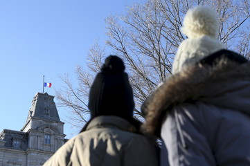 Two women look at the French flag flying at half-mast at Quebec's National Assembly in memory of the victims of the Paris attacks in Quebec City