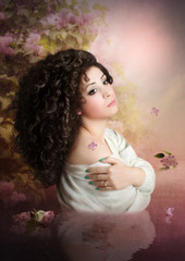 Dreaming girl with long, curly hair in the garden of lilac at sunset