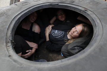 Supporters lie inside a tractor tyre at the Dale Farm Traveller site, near Billericay in southern England