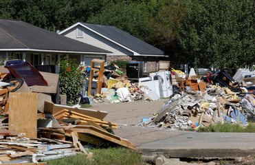 Debris is seen piled up in front of flood damaged homes in Prairieville