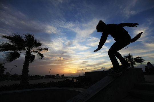 A teenager slides along a metal rail while skateboarding at the promenade in Ashkelon