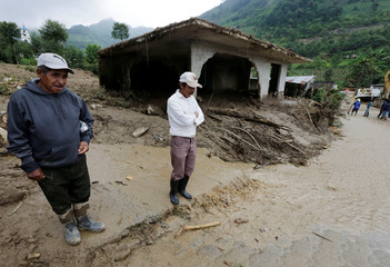 Residents stand beside a house, which was damaged by a mudslide, in the aftermath of Tropical Storm Earl in the town of San Miguel Xaltepec, in Puebla state, Mexico