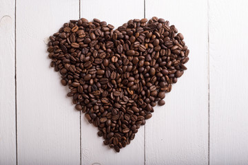 Coffee bean in the shape of a heart texture, background, copy plase. Place for text or inscription. Top view.
