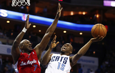 Charlotte Bobcats Walker works to shoot against Los Angeles Clippers Odom during NBA basketball game in Charlotte