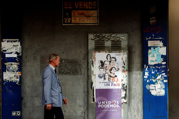 A man walks past posters of the coalition of Unidos Podemos hanging on an empty building for sale in Madrid
