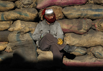 Afghan man working at a coal dump site waits for customers outside Kabul