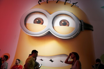 """Attendees walk past an Electronic Arts (EA) """"Minions Paradise"""" video game poster at the Electronic Entertainment Expo, or E3, in Los Angeles"""