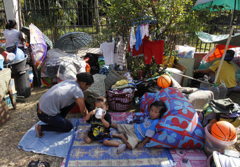 Families from a slum area evicted by workers from a government demolition crew, settle on the sidewalk with their belongings in Quezon City