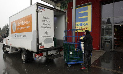 """A volunteer of the non-profit Dortmund food bank """"Dortmunder Tafel"""" loads donated fruit and vegetables that are not looking nice enough for sale into a sponsored van outside a super market in the western German city of Dortmund"""