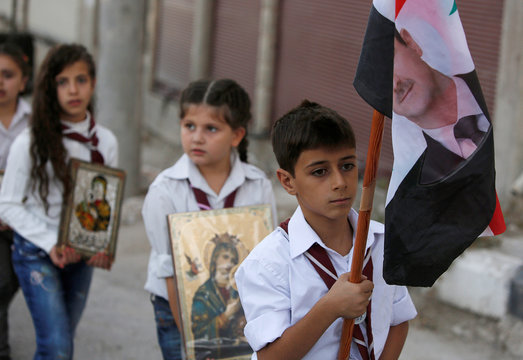 A boy carries a Syrian national flag depicting a picture of Syria's President Bashar al-Assad and girls carry icons of Virgin Mary during a parade, part of Saidnaya Festival, near Damascus