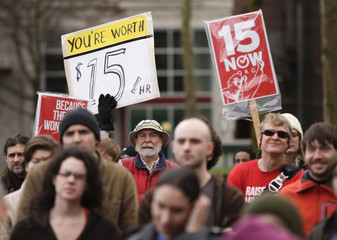 People rally in support of a $15 minimum wage at Seattle Central Community College in Seattle, Washington