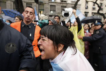 A sympathizer of former Argentine President Nestor Kirchner cries as others gather around the hearse carrying his remains in Buenos Aires